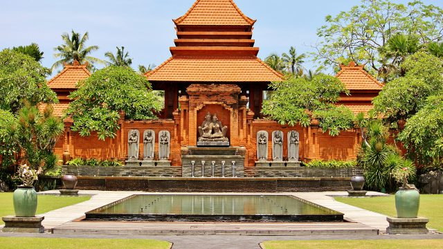 木々に囲まれたオレンジ色の寺院絵画