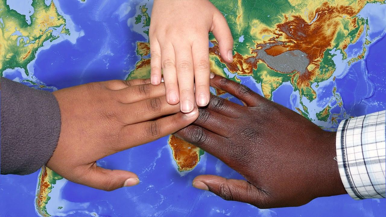 地球図の上にのせる3人の手